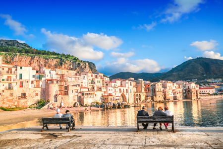 Photo pour People sit on benches by the sea with a view of Cefalu, Sicily, Italy - image libre de droit