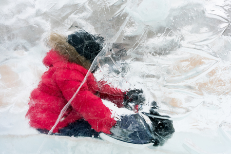 Little boy sitting on a sled behind a transparent ice