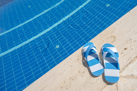 Photo for Edge of the pool with striped sandals - Royalty Free Image