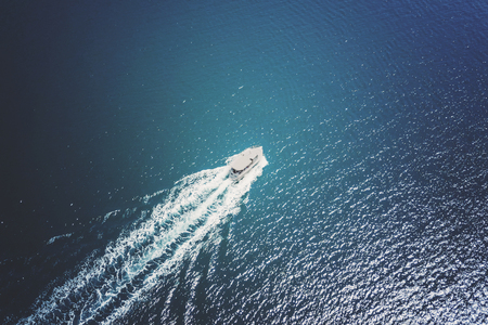 Foto de Top view of a white boat sailing in the blue sea - Imagen libre de derechos