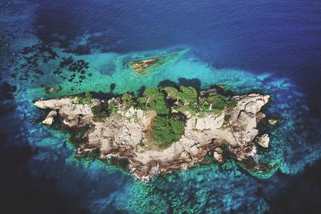 Foto de Top view of a rocky island with green trees in the sea - Imagen libre de derechos