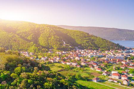 Foto de Beautiful city in the mountains near the sea in the sunlight, top view - Imagen libre de derechos