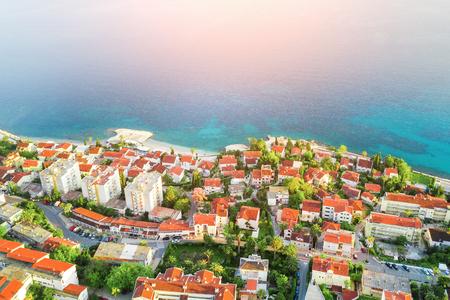 Foto de Seaside resort. City by the sea in the sunlight, top view. Houses with red-tiled roofs - Imagen libre de derechos