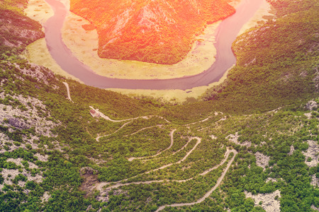 Foto de Top view of a winding highway and the river in the mountains on a sunny day - Imagen libre de derechos