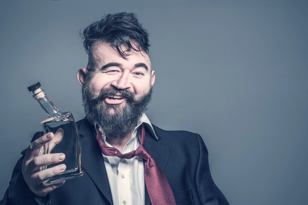 Foto de Distorted image of a bearded man in suit with a bottle of alcohol in his hand on a gray background - Imagen libre de derechos