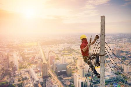 Foto de Electricians are climbing on electric poles to install power lines. - Imagen libre de derechos
