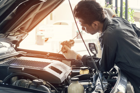 Photo pour Car mechanic in grey uniform are checking the level of the engine oil, Automotive industry and garage concepts. - image libre de droit