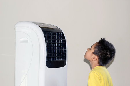 Photo pour Because of the hot weather, the boy stood by the fan blowing cold air to his face. - image libre de droit