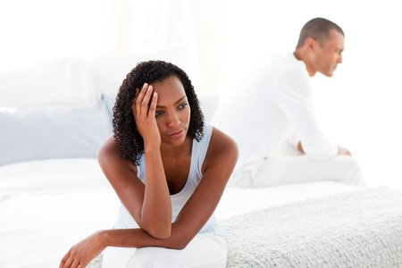 Upset young couple sitting on bed separately