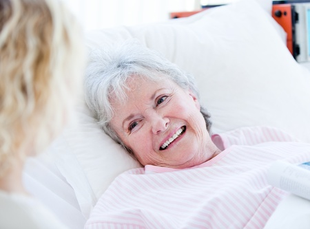 Smiling senior woman lying on a hospital bed talking with her granddaughter