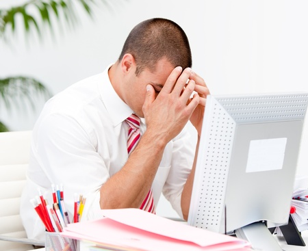 Frustrated businessman working at a computer