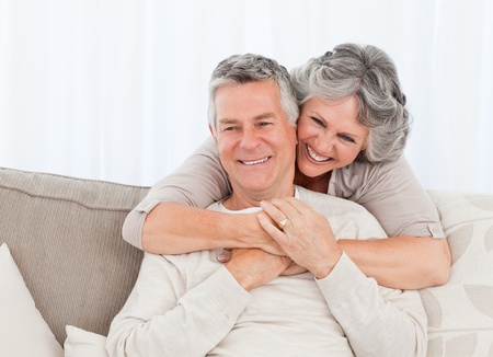Mature woman hugging her husband at home
