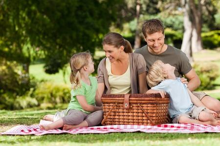 Photo pour Joyful family picnicking in the park - image libre de droit