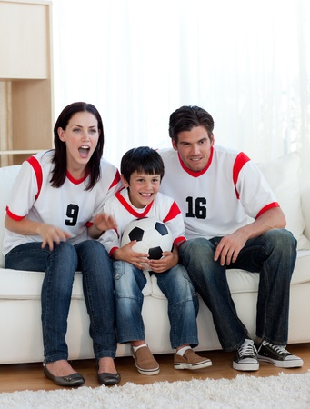 Parents and their son watching a football match