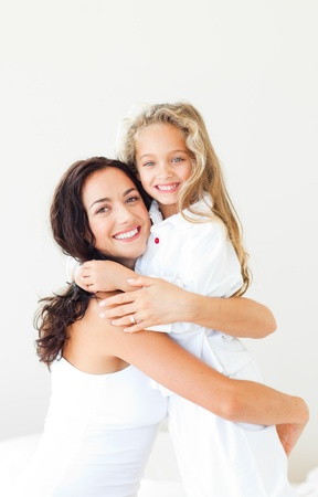 Photo for Joyful mother and her daughter looking at the camera on the bed - Royalty Free Image