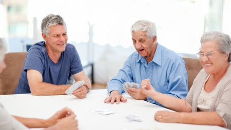 Photo pour Retired people playing cards together at home - image libre de droit