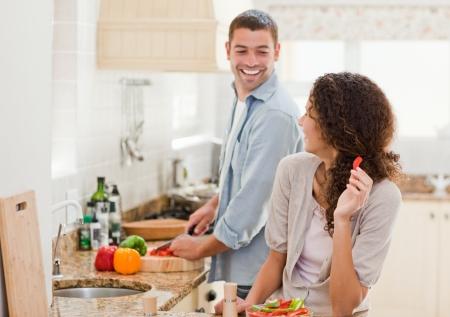Foto de Beautiful woman looking at her husband who is cooking at home - Imagen libre de derechos