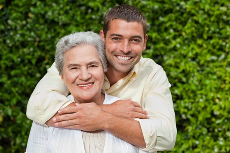 Photo for Man hugging his mother in the garden - Royalty Free Image