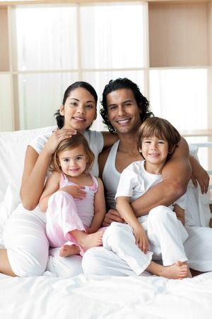 Portrait of a smiling family sitting on the bed