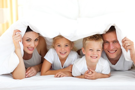 Photo pour Young family playing together on a bed  - image libre de droit