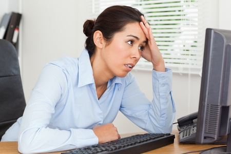 Beautiful upset woman looking at a computer screen while sitting at the office