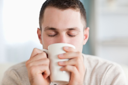 Calm man having a coffee in his living room