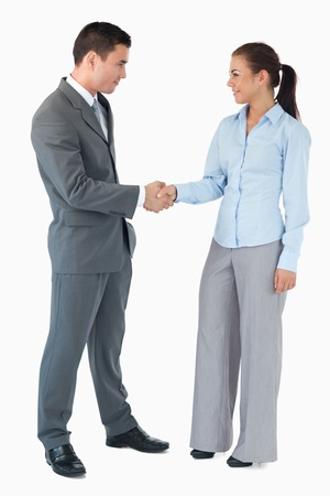 Confident business partner shaking hands against a white background
