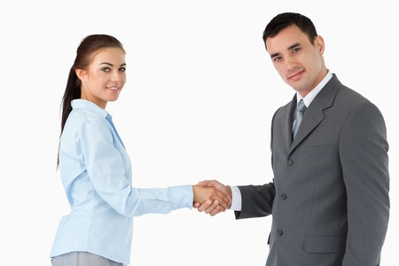 Young business partners shaking hands against a white background