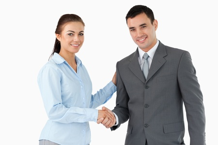 Smiling business partners shaking hands against a white background