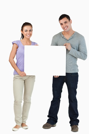 Photo for Young couple holding sign against a white background - Royalty Free Image