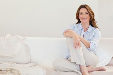 Smiling mature woman sitting on her sofa