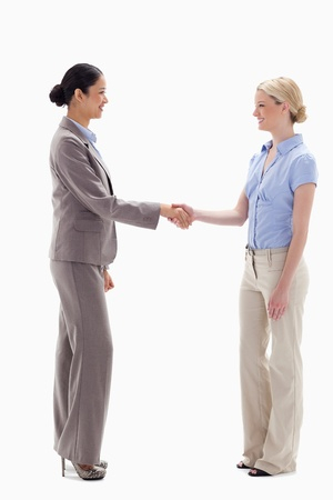 Women shaking hands happily against white background