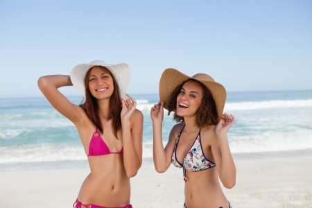 Happy young women sunbathing while standing in front of the sea side by side