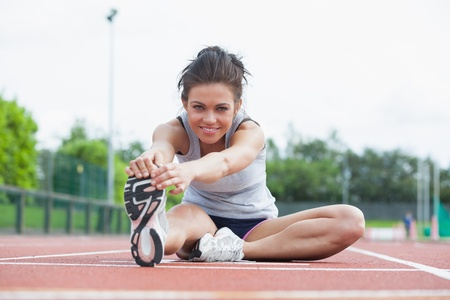 Foto de Woman stretching before race on track - Imagen libre de derechos