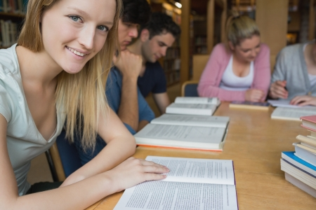 Smiling student with study group in college library