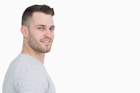 Photo for Side view portrait of smiling young man over white background - Royalty Free Image