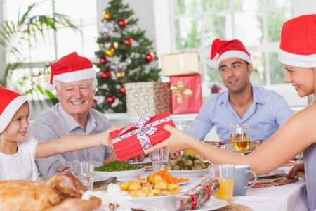 Mother giving daughter christmas present at christmas dinner