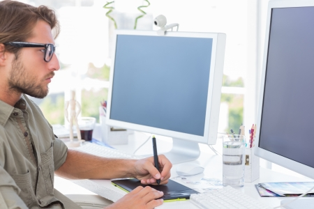 Photo pour Graphic designer using graphics tablet to do his work at desk - image libre de droit
