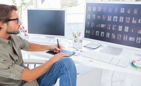 Photo for Photo editor using digitizer to edit at desk in modern office - Royalty Free Image