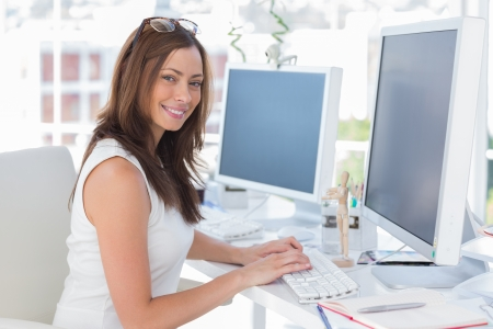 Photo for Female designer at her desk smiling at the camera - Royalty Free Image