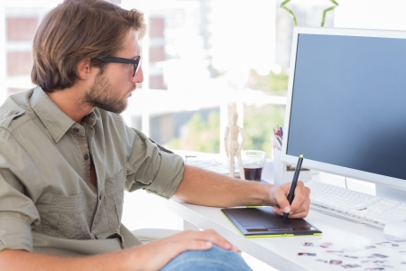 Foto de Artist using graphics tablets sitting at desk - Imagen libre de derechos