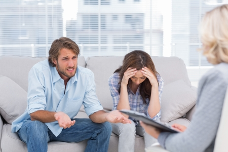 Foto de Young couple sit on the couch of the therapist and the woman is crying - Imagen libre de derechos