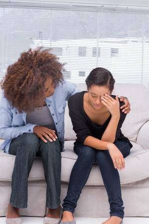 Foto de Woman crying next to her therapist who is comforting her - Imagen libre de derechos