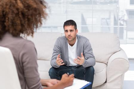 Foto de Depressed man speaking to a therapist while she is taking notes - Imagen libre de derechos