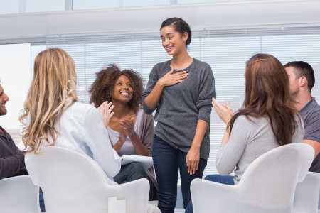 Foto de Happy patient has a breakthrough in group therapy while others are clapping her - Imagen libre de derechos