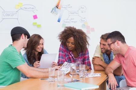 Foto de Creative team going over contact sheets in meeting in office with whiteboard - Imagen libre de derechos
