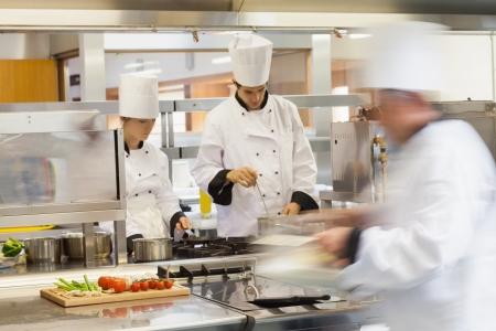 Photo pour Busy chefs at work in the restaurant kitchen - image libre de droit