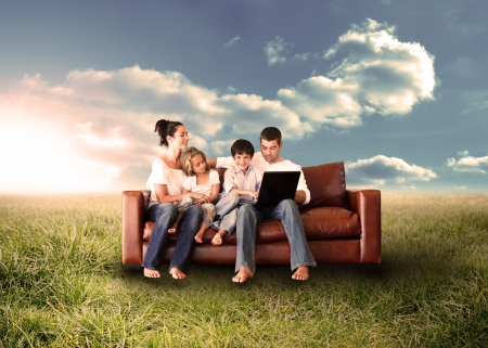 Foto de Happy family in the couch using the laptop in a sunny field in the countryside - Imagen libre de derechos