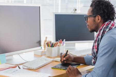 Foto de Graphic designer using a graphics tablet in a modern office - Imagen libre de derechos