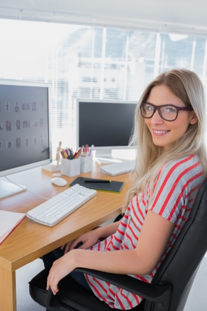 Photo for Portrait of a smiling photo editor in a modern office - Royalty Free Image